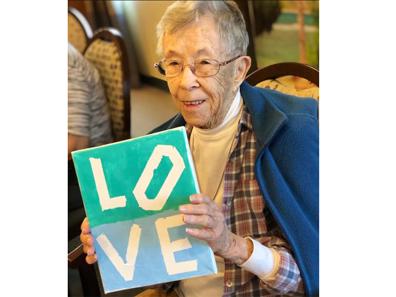 A resident holding a clay painting that reads 'love'.