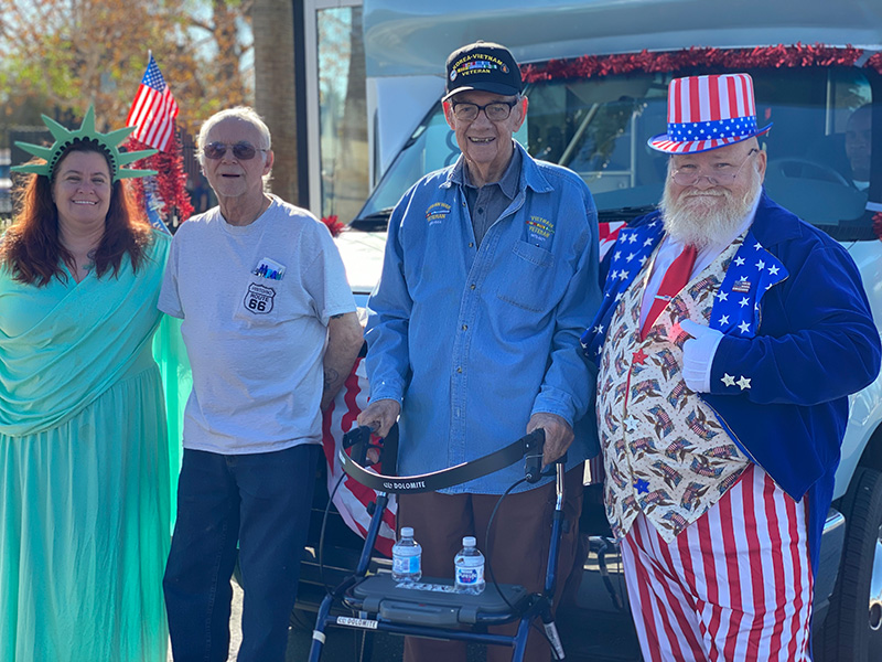 A group standing outside with two of the four dressed patriotically.