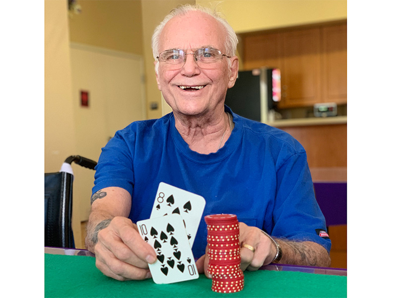 A resident playing cards with poker chips beside his cards.