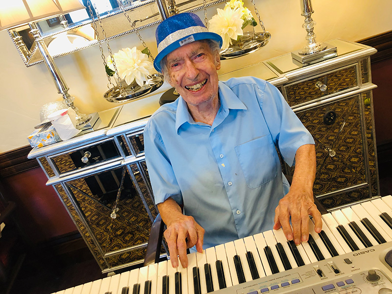 A resident happily playing the piano.
