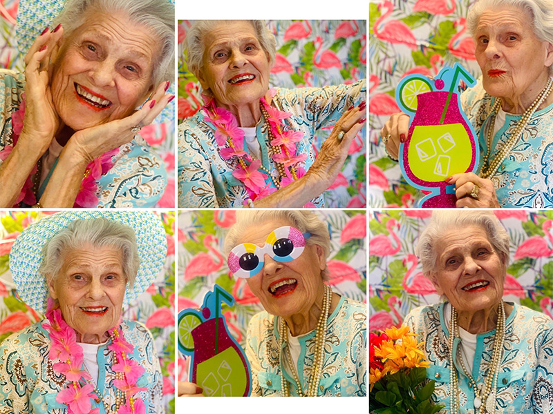 Beautiful resident smiles and poses as she switches from holding flowers to holding tropical drink props during a Hawaiian themed photoshoot. She even spices it up with some fun beach ball sunglasses and floppy hat.