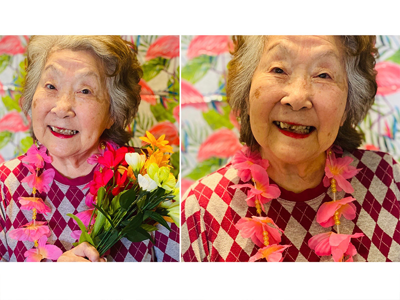A cute resident smiling as she holds tropical flowers and wheres a flower necklace. She is in a fun Hawaiian themed photoshoot