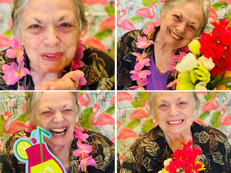 Lovely resident smiles and blows kisses as she poses for the Hawaiian themed photoshoot. She dresses in a flower necklace and holds exciting tropical drink props. She looks stunning the whole time.