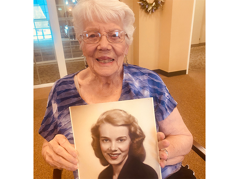 A resident holding up an image of herself when she was a young woman.