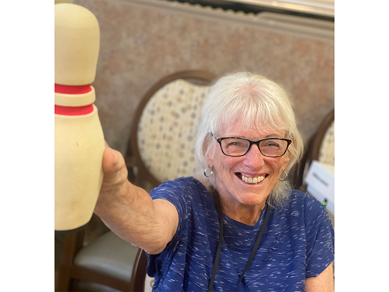 A resident holding up a bowling pin.