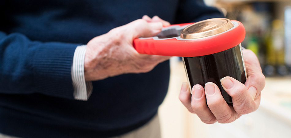 A close up photo of an elderly man's hands using a tool to open a jar