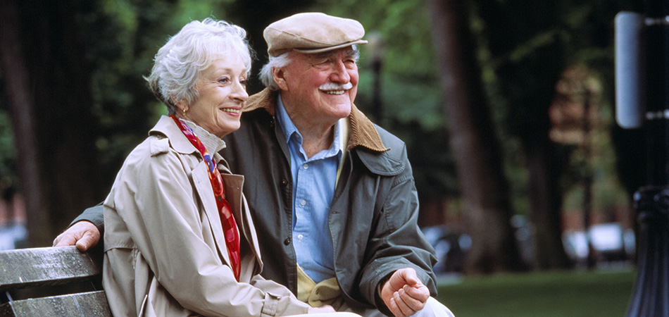 Smiling elderly couple seated on a bench outside