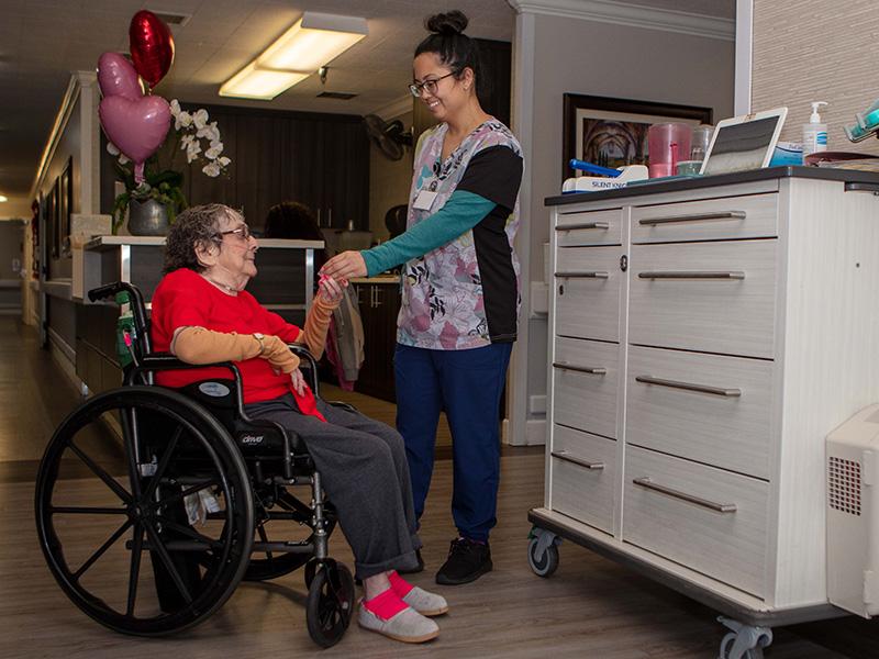 Nurse with a woman in a wheelchair.