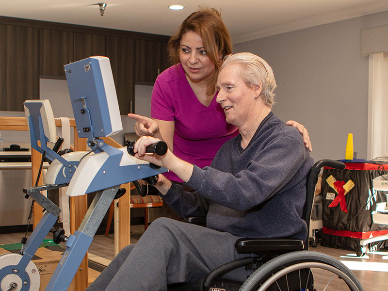 Nurse with woman in physical therapy.