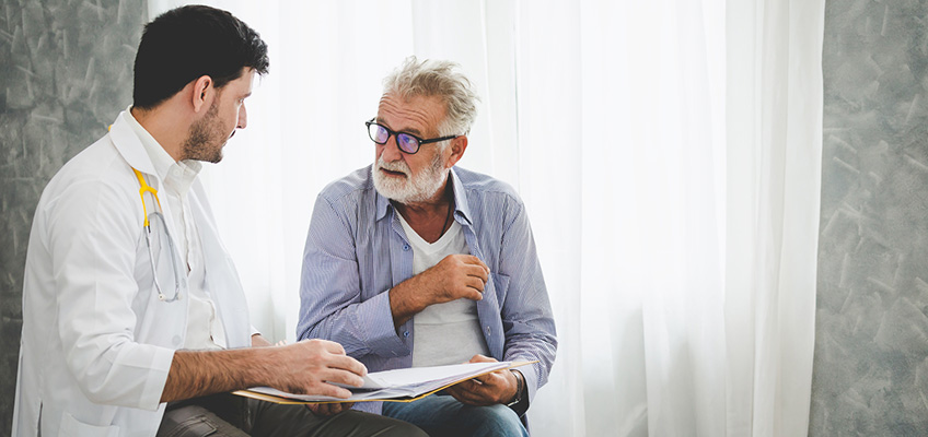 A doctor sitting with a patient going over his chart.