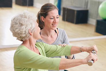 A woman assisting a senior woman with dumbbell exercises.