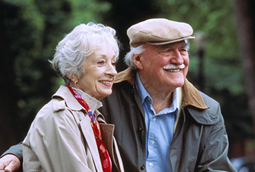 A couple sitting in a park-like setting with smiles.