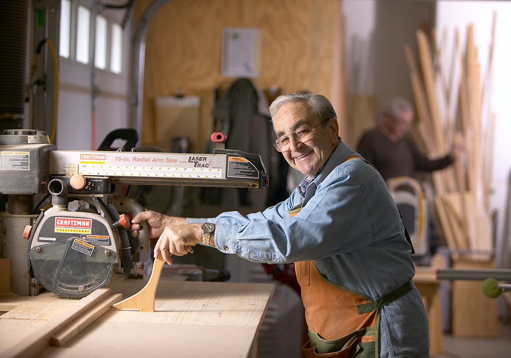 A man cutting wood, smiling and happy