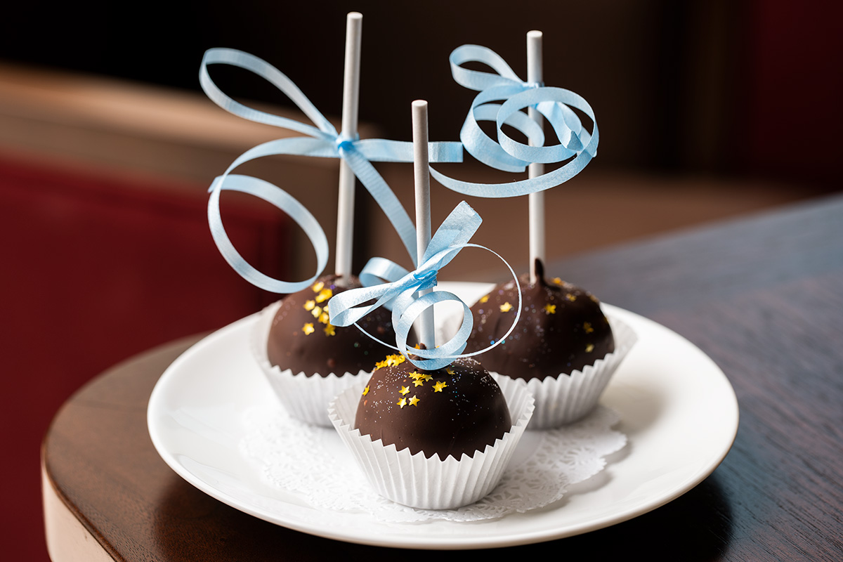 Delicate chocolate cakepops with star sprinkles and blue ribbon tied around