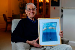 Resident holding a picture of parachuters descending into the water