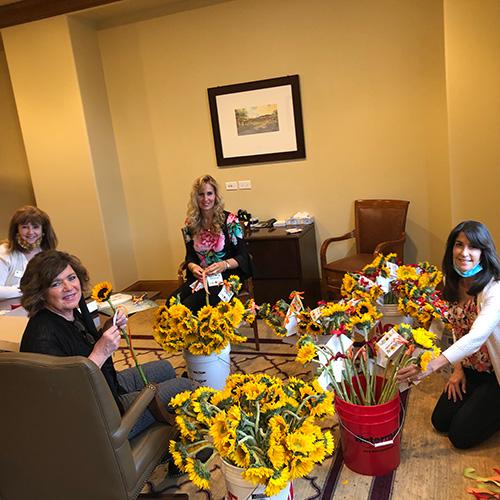 women putting flowers in buckets