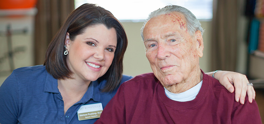 Smiling therapist with her arm around a resident's shoulder