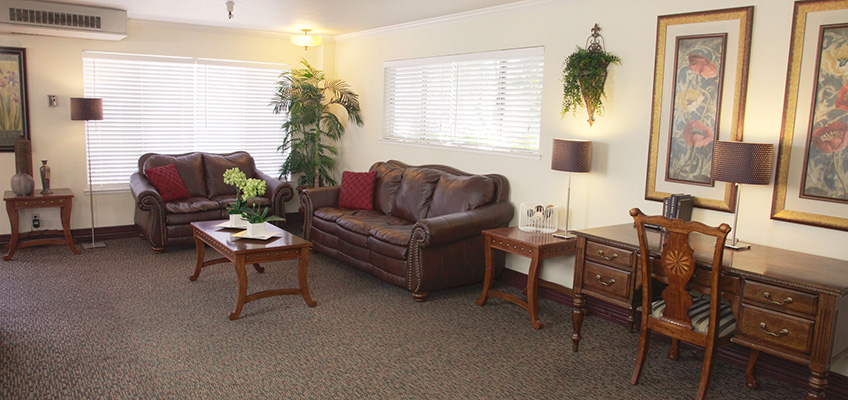 Roseville seating area with plush leather couches and plants and artwork on the walls