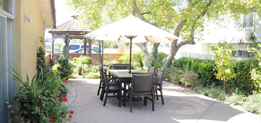 Beautiful outdoor patio set with umbrella and situated underneath a shade tree. There is a gazebo in the background too.
