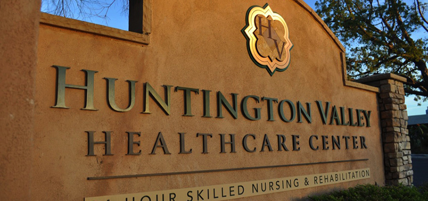 Huntington Valley exterior sign made of stucco with raised gold lettering and stacked stone pillars