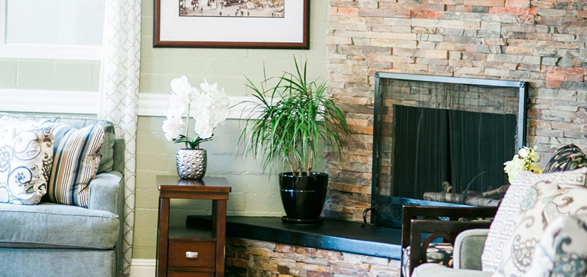 A lobby with a fireplace and plants beside it on a table.