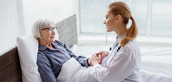 nurse sitting with resident in bed