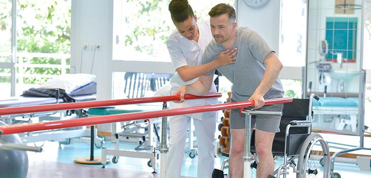 nurse helping a man with physical rehabilitation