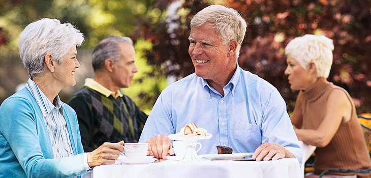 elderly couple smiling together at the table eating