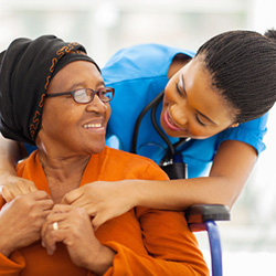 Woman seated in a wheelchair reading with a nurse