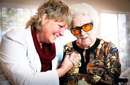 Resident and staff member smiling holding hands
