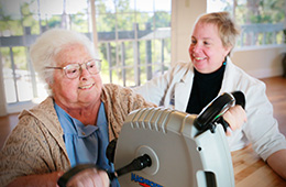 Resident using a rehab bike with staff member smiling next to them