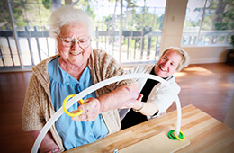 Resident using physical therapy equipment smiling with staff member