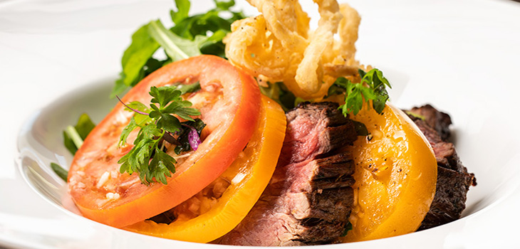 A plate of thinly sliced steak in a bed of fresh tomatoes and arugula.