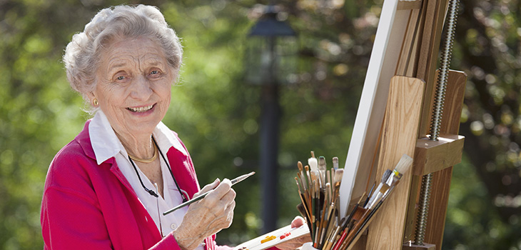 A senior outside painting.