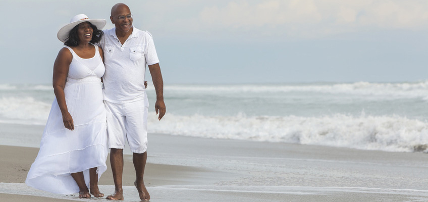 A couple both wearing white nice clothes walking down the beach on a gloomy day