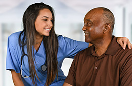 A nurse and patient smiling at each other.