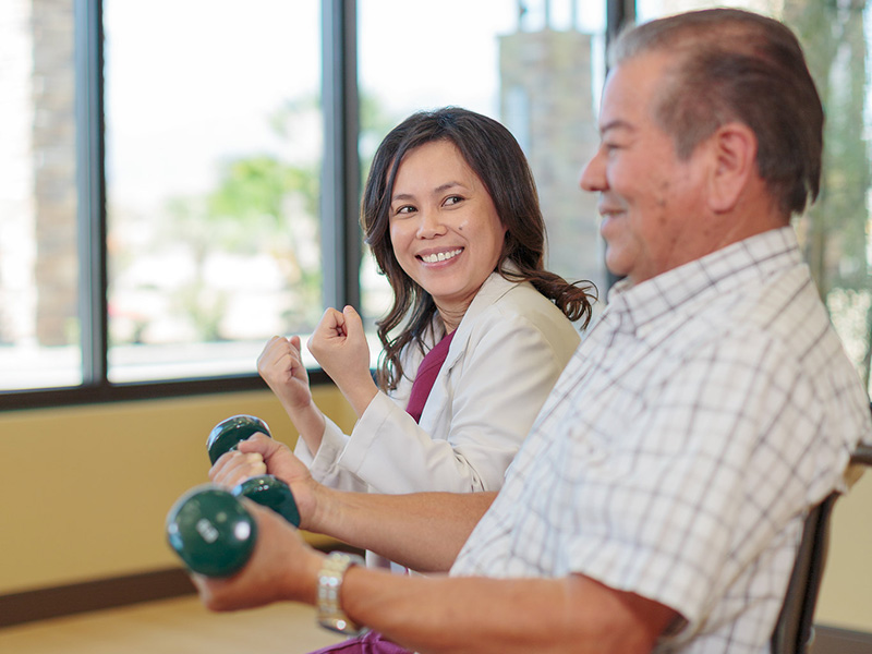 Physical therapist and resident working together lifting weights