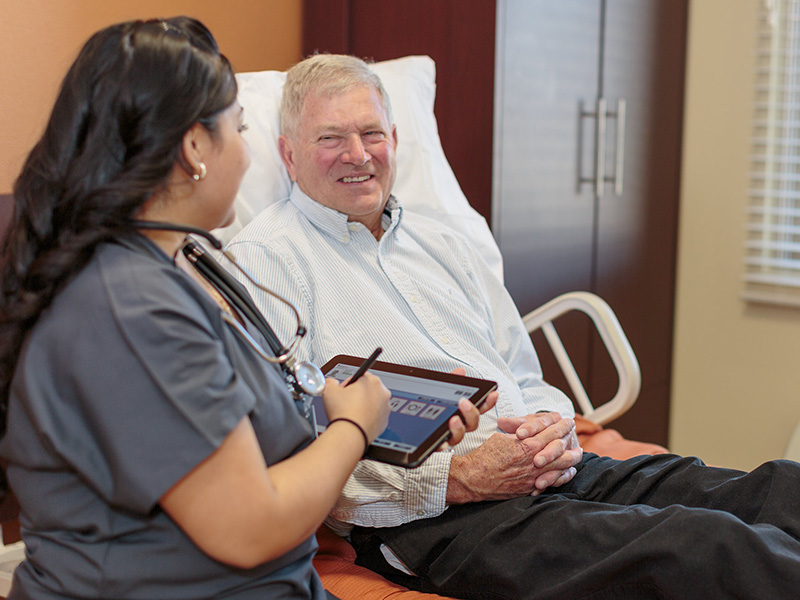 Certified Nursing Assistant smiling and laughing with resident