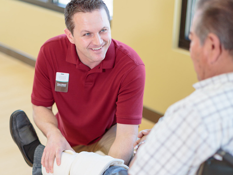 Physical therapist smiling while helping resident