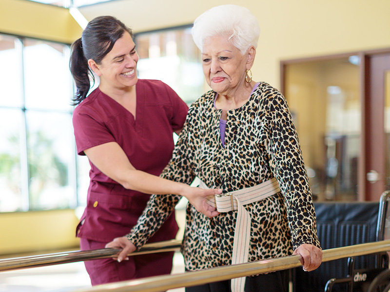 Physical therapist and resident smiling working together