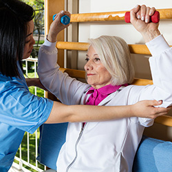 Elderly woman using hand weights with a trainer