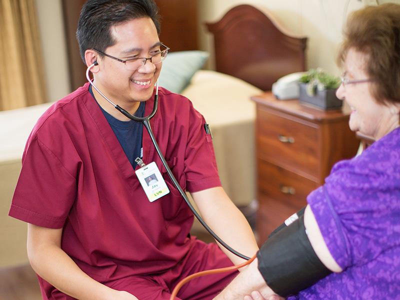 Nurse taking resident's blood pressure