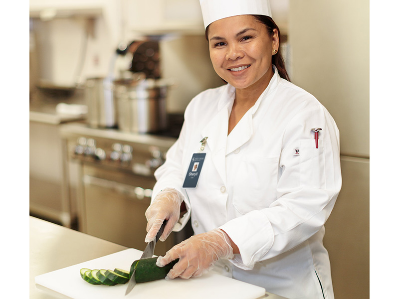 A staff member happily preparing food in the kitchen.
