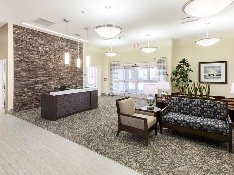 A stone wall behind a receptionist desk with several options for seating.