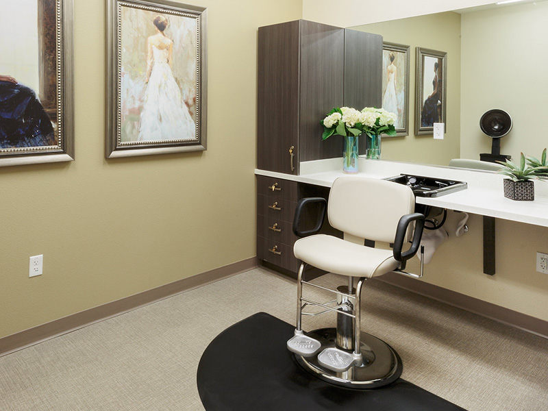 A clean resident salon with images on the wall and flowers on the counter.