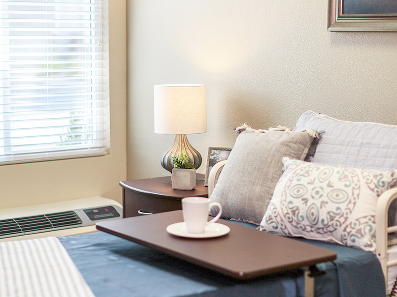Resident room with nicely made bed and a nightstand with lamp, plant and image.