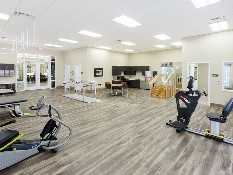Large rehabilitation gym with wood floors and organized equipment.