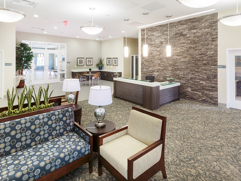 Lobby area with a stone wall, receptionist desk, and several options for seating.