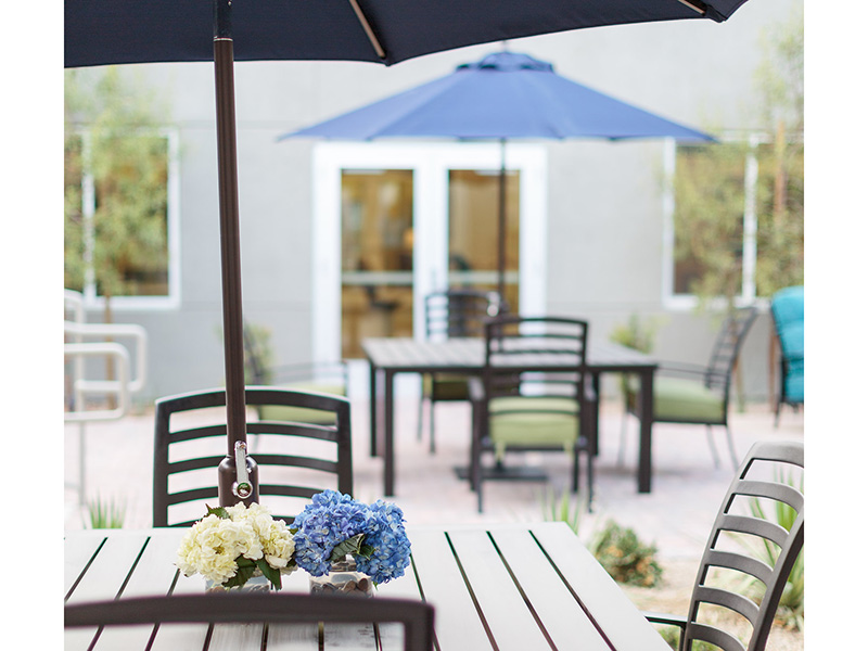 Outside seating with shaded options and flowers on the table.