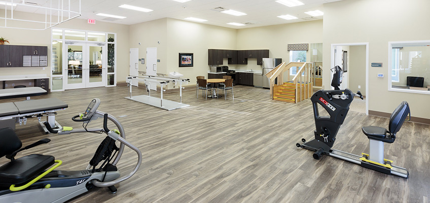 Rehabilitation room with clean, wood floors and spaced out equipment.
